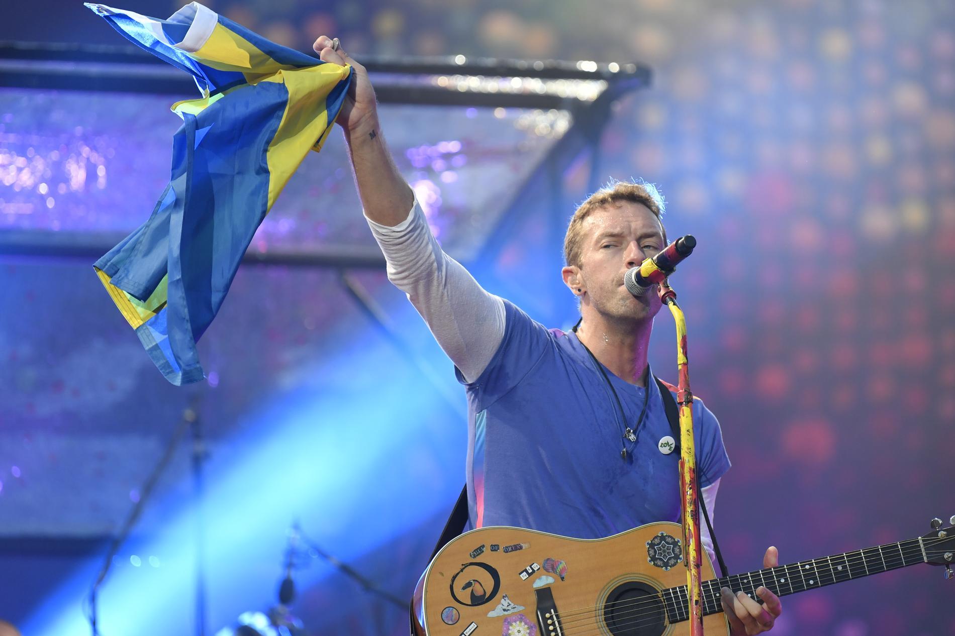 Chris Martin lyfter en svensk flagga under en spelning på Ullevi i Göteborg 2017. Arkivbild.