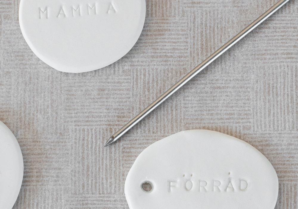 En liten nål kan användas för att lägga till prickar på vissa bokstäver.