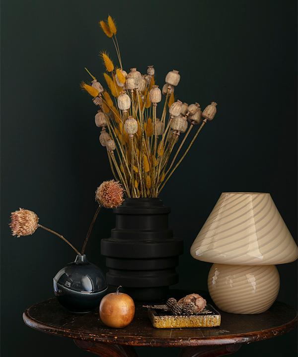 Den svarta vasen med torkade blommor är från en vän. Den är från märket dbkd. Bordslampan i glas är från Sudio Lys