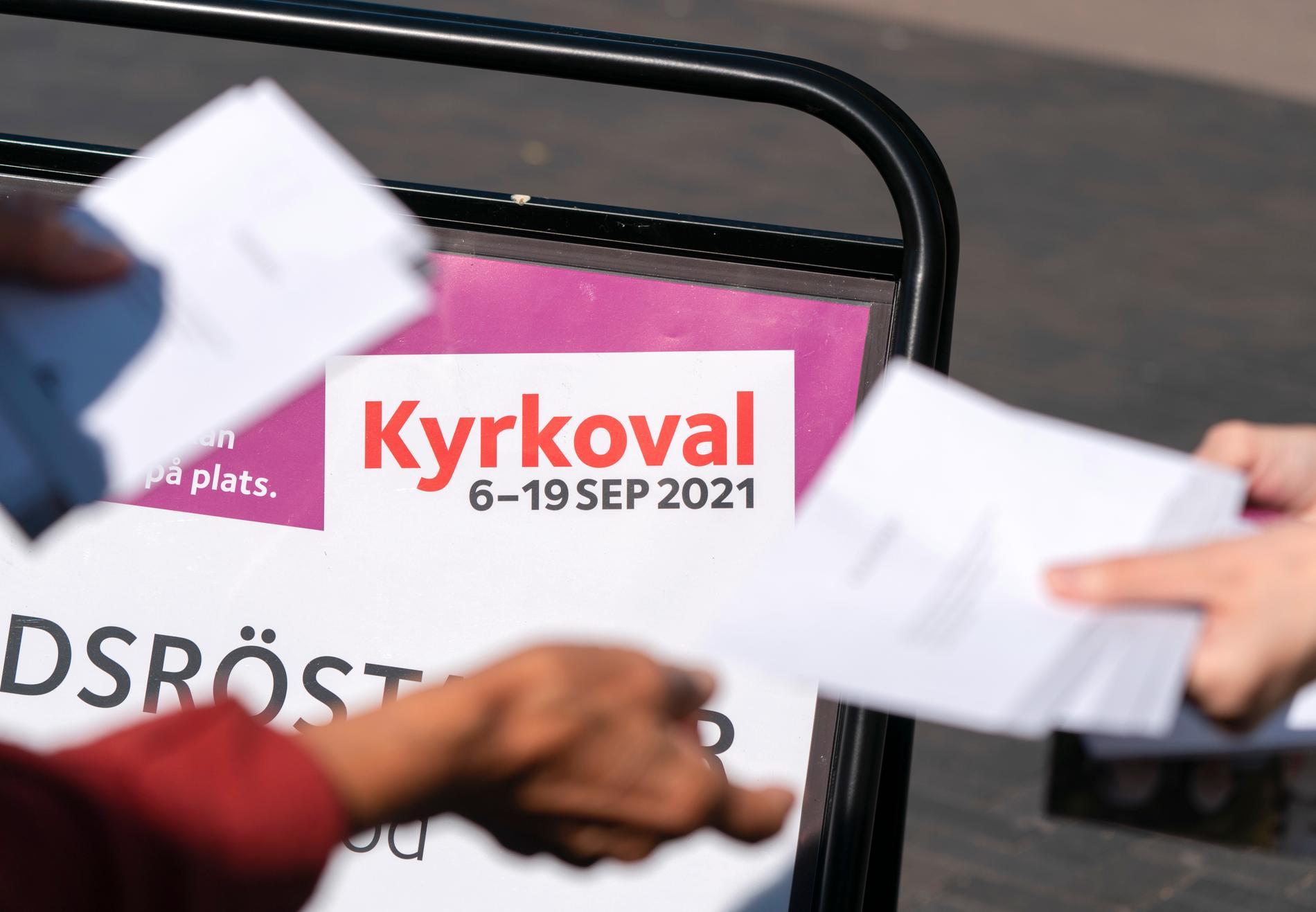 Valkuvert delas ut till röstande utanför lokalen för förtidsröstning i kyrkovalet 2021 vid S:t Johannes kyrka vid Triangeln i Malmö.