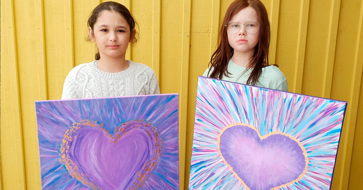 Alexandra och Nova-Li med några av de tavlor som auktionerats ut för att hjälpa andra barn.