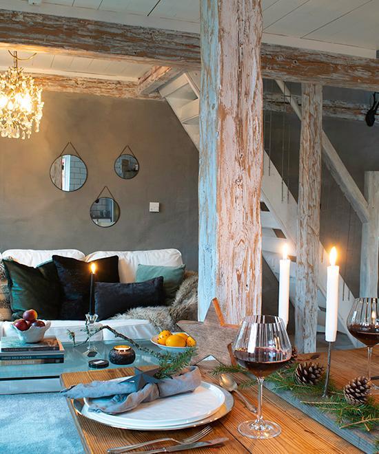 Från hallen kommer man direkt in i vardagsrum och kök. De vackra bjälkarna i lägenheten är vitlaserade och minner om husets ålder.