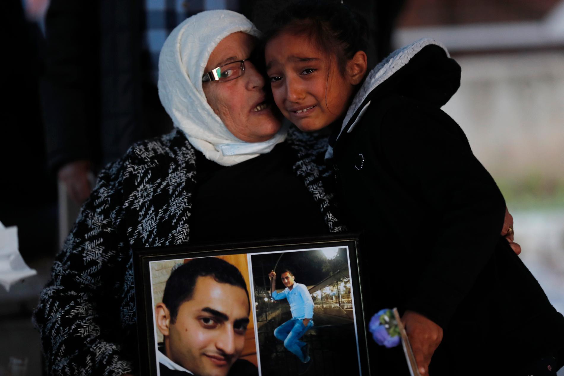 En flicka kramar om sin farmor, som bär på porträtt av en son som omkom i hamnexplosionen i augusti i fjol. Arkivbild.