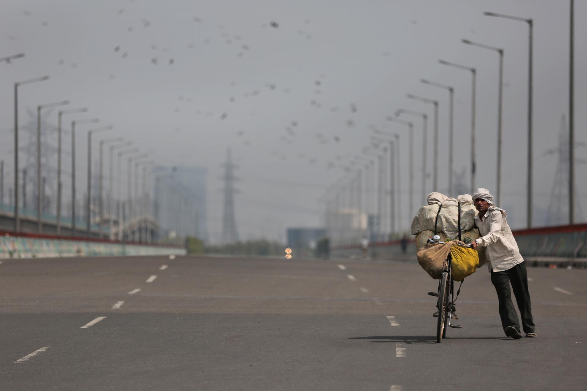 Hela Indien sätts i ett slags karantän. Här går en ensam grönsakshandlare med sin cykel på en väg i Noida utanför huvudstaden New Delhi.