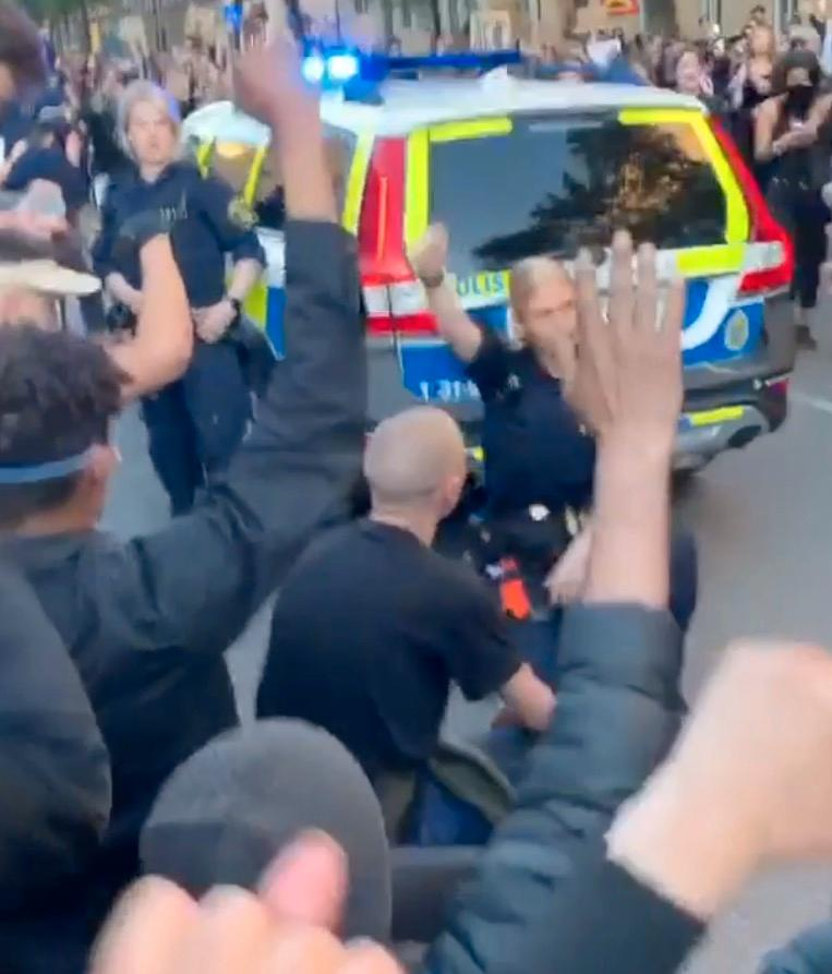 Polis går ned på knä tillsammans med demonstranter.