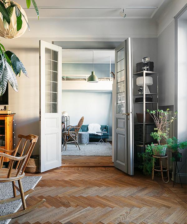 När Lotta flyttade in i lägenheten slipade hon golv, målade väggar, lister och dörrar. Här ser man de fint bevarade dubbeldörrarna mellan vardagsrummet och sovrummet.