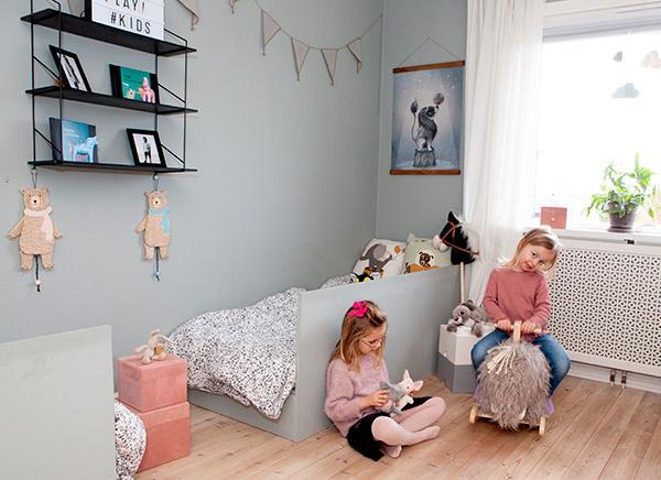 Systrarna Elsa och Thilde i tvillingarnas rum. Sängarna är byggda av pappa Daniel och målade i samma färg som väggen, Nordsjös kulör Tant Johannas gröna. Vimpel och posters från Mrs Mighetto, hylla från Netto och sprattelbjörnar från Bloomingville.