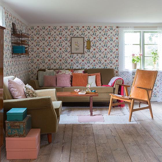 I vardagsrummet har Sten satt upp tapeten Karlslund Tessin från Boråstapeter. Soffa med tillhörande fåtölj, bord och trasmattor loppis, läderfåtölj köpt på nätauktion, mönstrade kuddar Svenskt tenn, vit kudde Ikea, resten loppis.