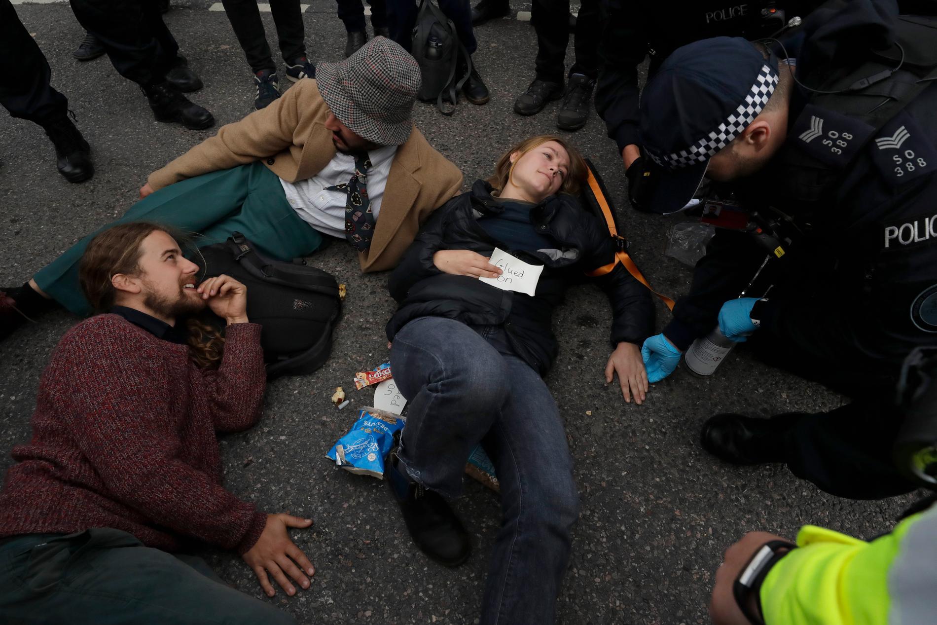 Det var fler än James Brown som limmade fast sina händer under miljöprotesten i London. Här hjälper polisen en kvinna som limmat fast handen i marken. Arkivbild.