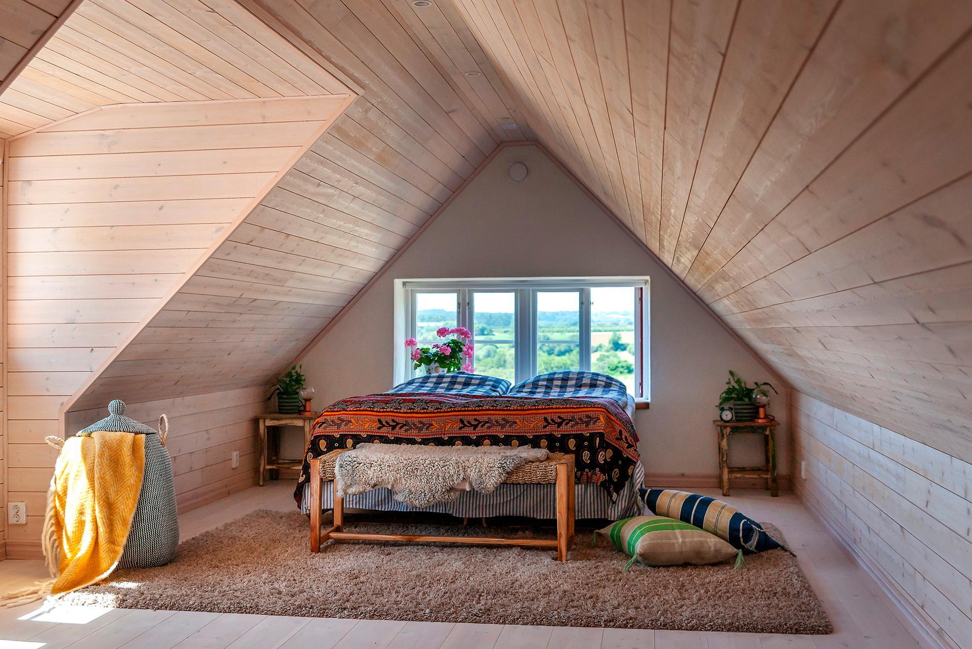 I den nya längan har Anders sitt sovrum en trappa upp. Härifrån är utsikten över Österlens böljande kullar bedövande vacker. Överkast från Apotekarns.
