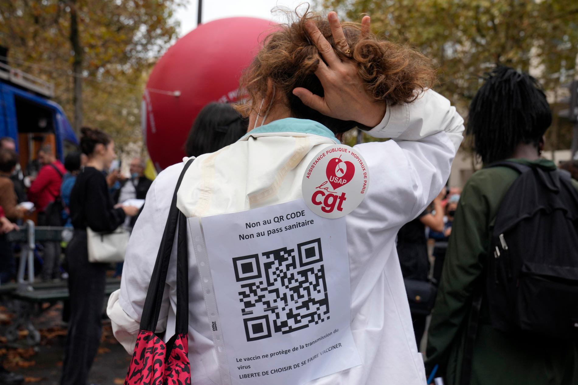 """""""Nej till QR-kod, nej till hälsopass, vaccinet stoppar inte virusets spridning – frihet att välja om man vill bli vaccinerad"""", står det på ryggen på en vårdanställd som protesterar mot beslutet."""